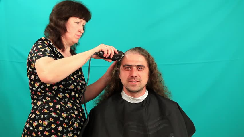 Man having an haircut on the green background, timeLapse