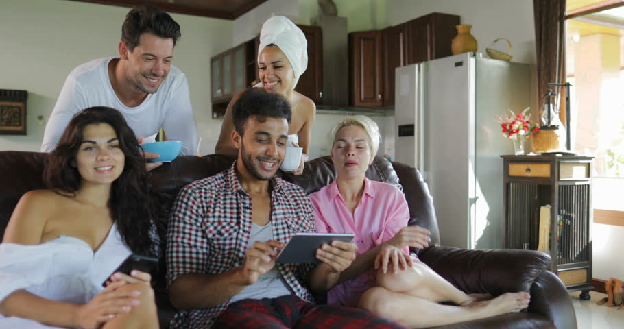 Young People Group Morning Watch TV Sit On Coach In Modern Studio Apartment Talking Use Tablet Computer Slow Motion 60 | Shutterstock HD Video #29311201