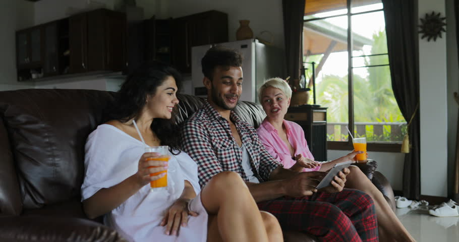 People Use Tablet Computer On Coach Watching Tv In Living Room Drink Juice, Young Man And Woman Group In Morning Talking Modern Apartment Interior Slow Motion 60   Shutterstock HD Video #29315821