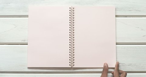 A male hand open diary paper 3 page  on the white wooden desk, top view and overhead shot use for blank template book mock up to add any text content