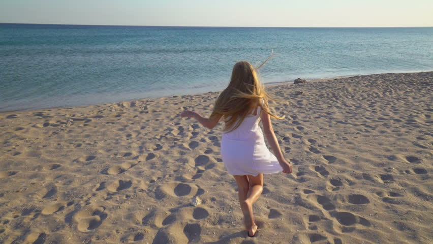 Young happy girl with long blonde hair running across sandy beach towards the sea. Barefoot teen girl in short white dress having fun during summer holidays vacation. Gimbal shot.