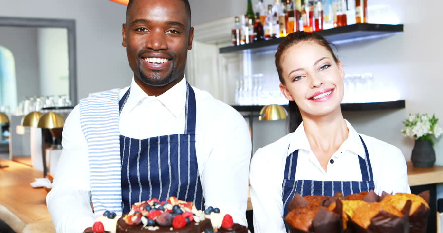 Portrait of smiling waiter and waitress presenting desserts at counter in resturant