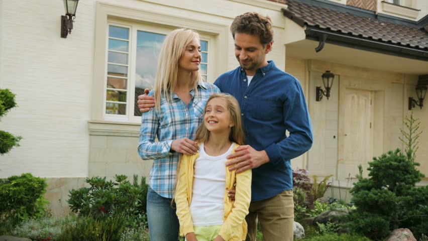 Emotional beatiful couple hugging their daughter and smiling on camera in front of new house.