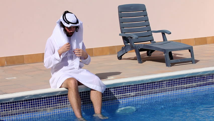Saudi Arabian man with his feet in water swimming pool