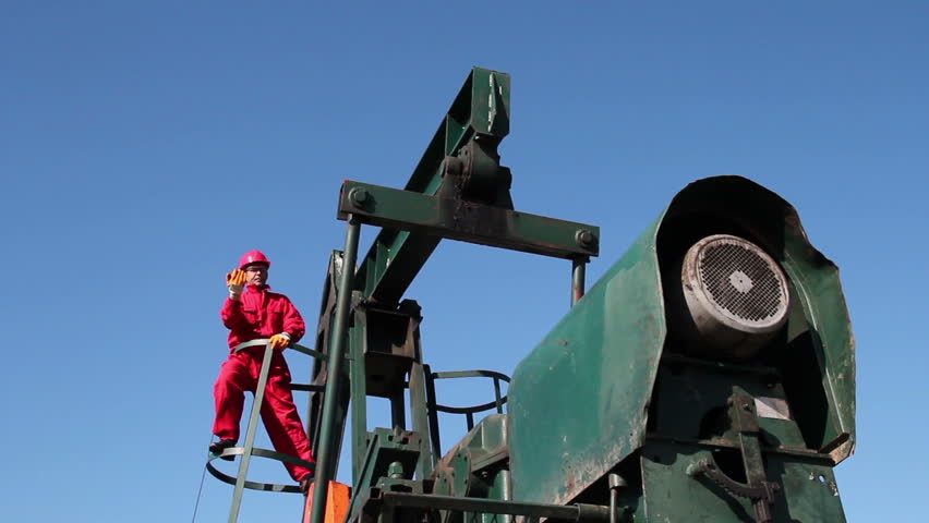Worker Standing at Oil Pump Jack. Worker in action at pump jack oil well. HD1080p.