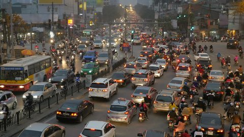 Rush hour in Hanoi, Vietnam, crowded traffic mess at intersection with cars, motorbikes, buses and many people. High angle, long shot.