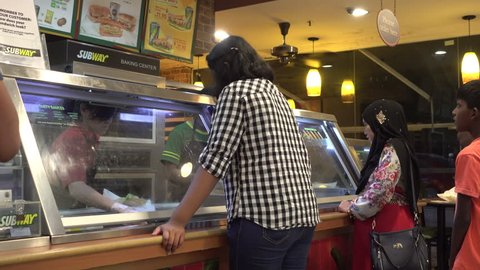Malaysia, Circa 2017 - Malaysians lining up and ordering Subway Sandwiches at Subway Restaurant, a fast food restaurant franchise that primarily sells submarine sandwiches (subs) and salads.