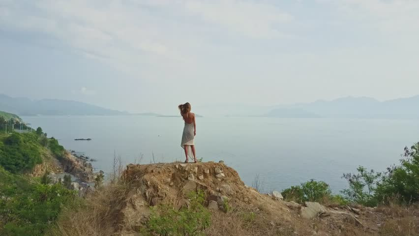 Drone removes from blonde girl stretching on hill top against majestic panoramic view calm sea and mountains