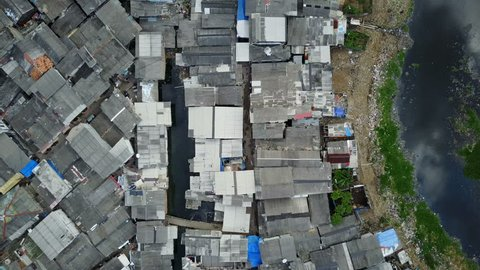 Overhead drone shot flying over rooftops of makeshift slums in Jakarta, Indonesia