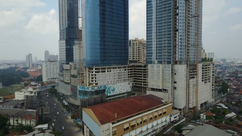 SURABAYA, INDONESIA - APRIL 2017: Rising aerial shot of office towers and construction site in downtown Surabaya Indonesia