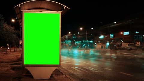 Blank green screen advertising billboard on street at night with traffic time lapse, useful for chroma keying