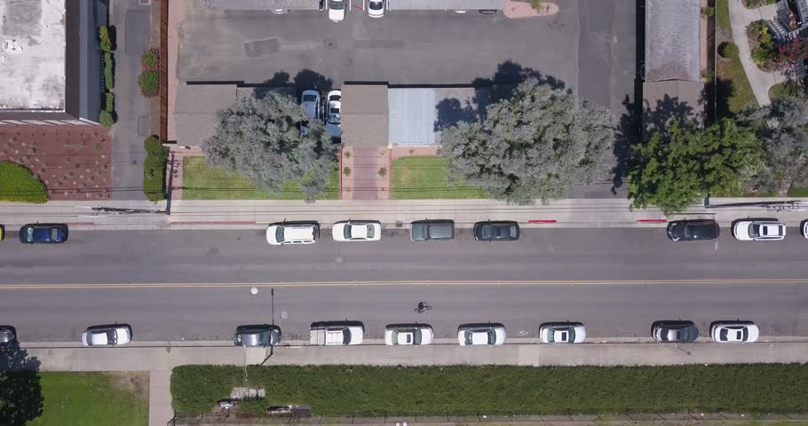 Ariel view of biker in the California suburbs, Ariel view of flying over houses following a biker. Ariel view of biker on road with cars and houses.  | Shutterstock HD Video #29501971