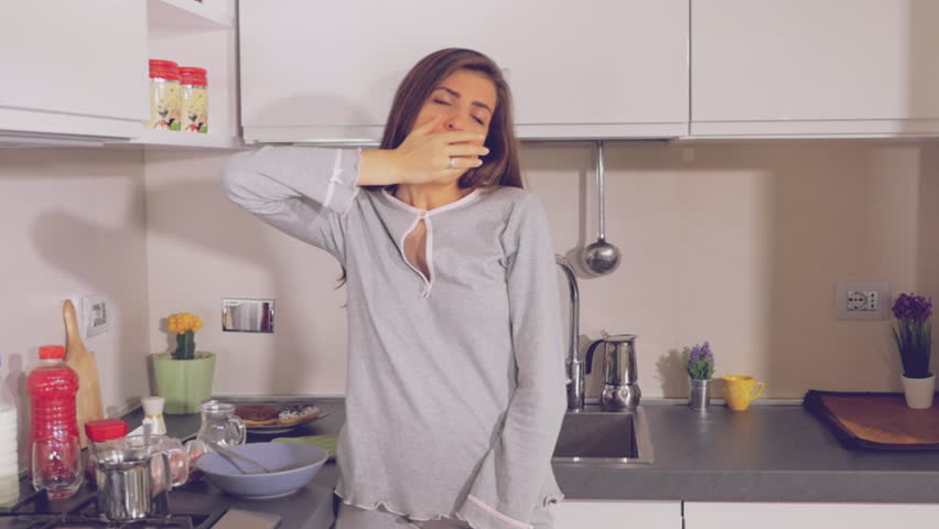 Cute woman tired in the morning yawning and stretching in kitchen slow motion