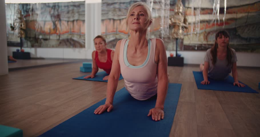 Active senior woman stretching her body and exercising by doing pilates in a fitness studio
