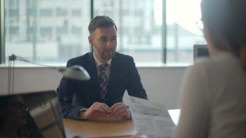 Man goes to job interview, sits and desk and is being interviewed by female boss, nervous and anxious he fiddles with a pen as she checks over his CV.