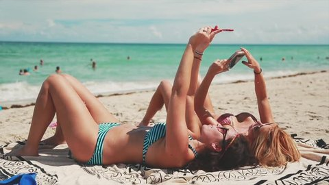 Two girls taking selfies while laying down at beach