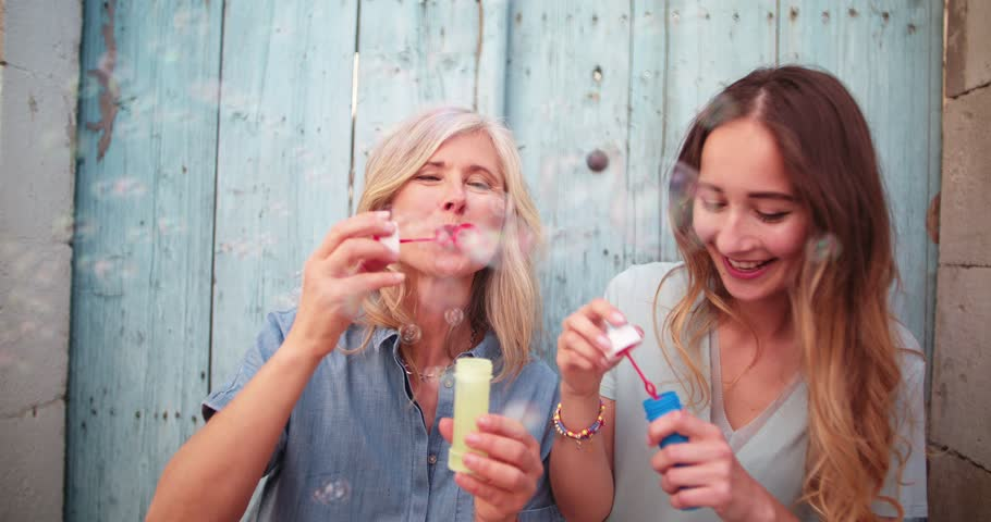 Happy mature mother and teenage daughter blowing bubbles and laughing in old city streets