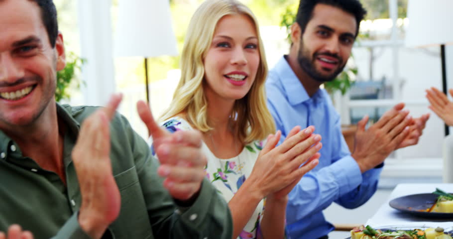 Smiling Friends Applauding While Having Meal In Restaurant