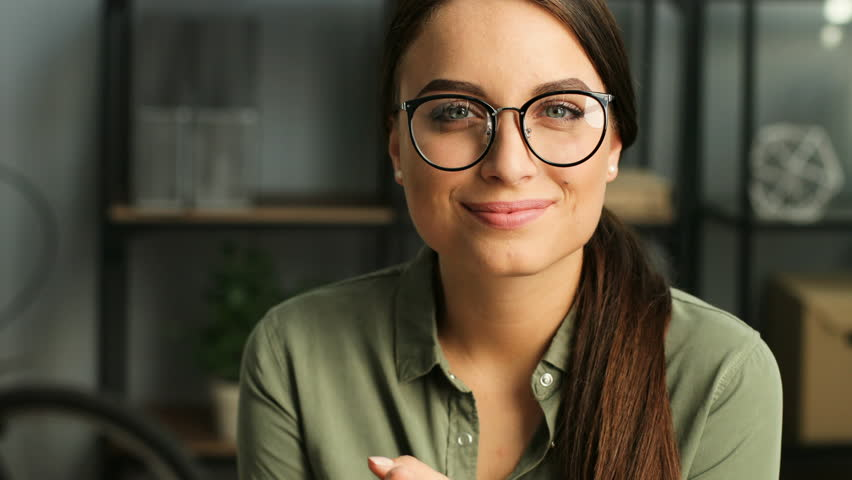 Portrait shot of attractive woman looking at the camera and smiling while working in the urban office. close up