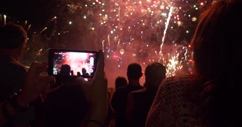 People Filming and taking pictures of Fireworks Display. Beautiful moving particles background and glitter USA 4th of July New Year Celebration video and photo technology crowd holidays memories 4k