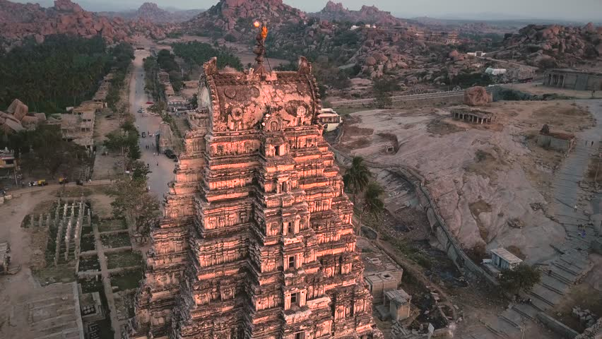 Sunset overlooking the top of the ancient Virupaksha temple, Hampi, Karnataka, India. The river and the temple complex in the background