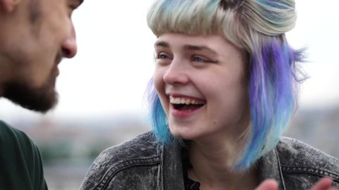 Close up of freaky girl with colored hair and youngster sitting on the roof above the city and laughing with each other