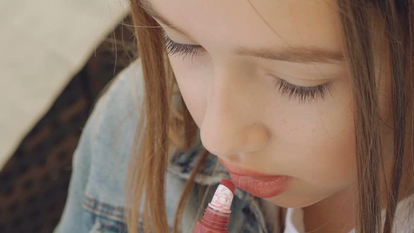 Pretty female teen applying the lipstick on the lips. Slowly