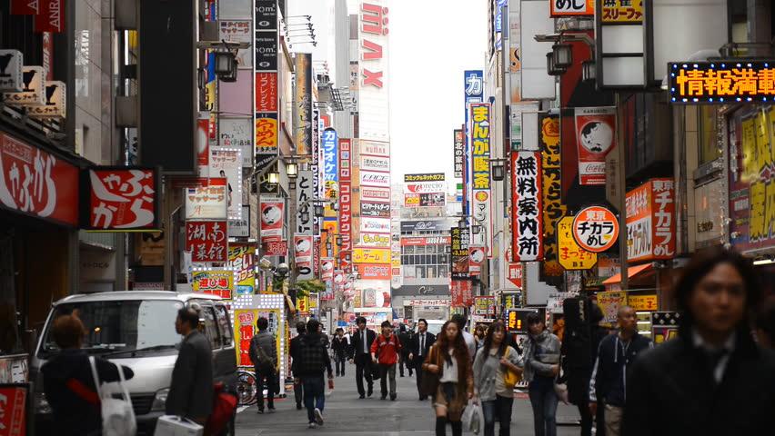 TOKYO, JAPAN - APRIL 12, 2012 Shinjuku Neon Sign Street, Shopping Area in Tokyo, Japan, Day Traffic Crowds