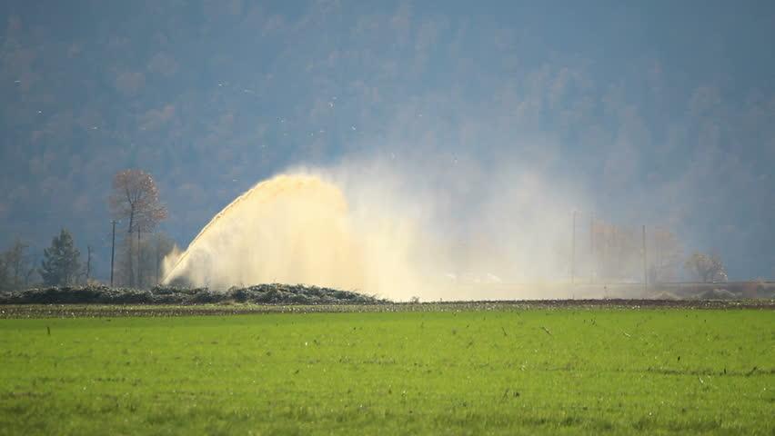 A high pressure hose is used to irrigate and fertilize a farmer's field/High Pressure Irrigation and Fertilization/A hose and strong winds spread moisture and fertilizer across a farmer's field | Shutterstock HD Video #2970178