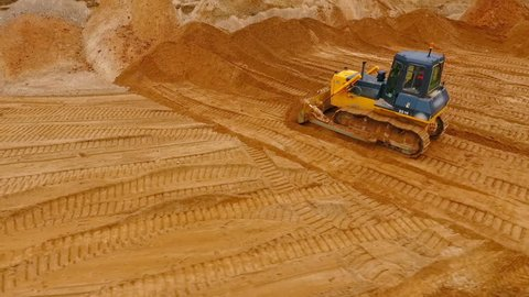 Bulldozer machine moving sand in sand quarry. Mining equipment at quarry. Crawler bulldozer moving sand. Aerial view of crawler bulldozer mining sand