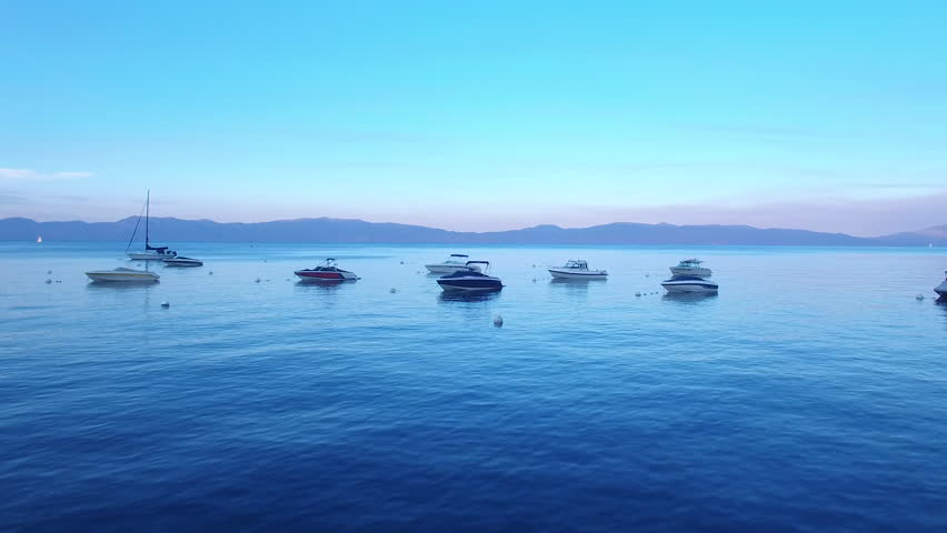 Aerial sunset lift off on Lake Tahoe. The Lake is beautifully highlighted by a boat dock and boats with a scenic snowy summer sunset mountain landscape in Lake Tahoe.4k 30fps July 15, 2017.