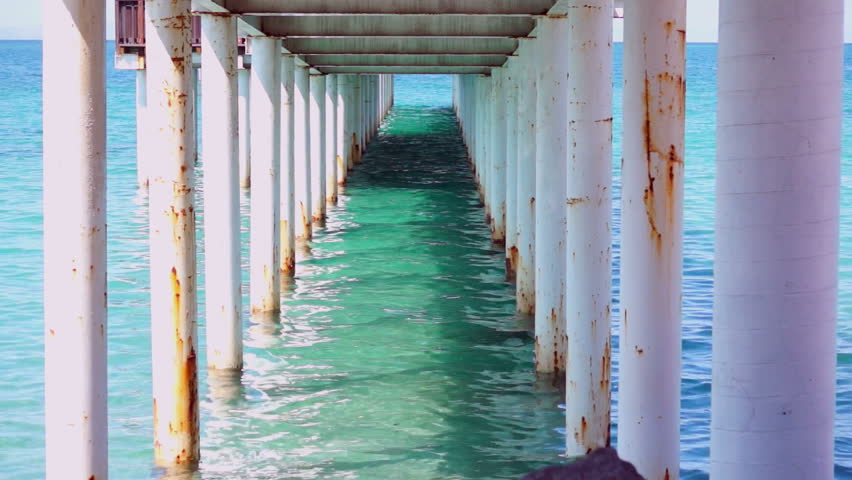 A still shot of the turquoise water and the pillars under the boardwalk down at the ocean.