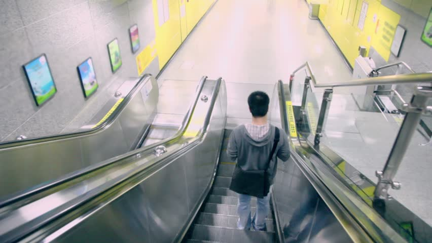 Man moves down on escalator, shown in motion from behind in metro