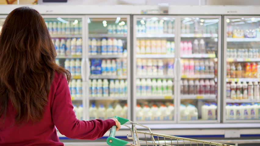 Advertise, Business, Food, Health Concept -  Woman in a supermarket standing in front of the freezer and choose buying fresh milk bottle. Drink milk for healthy. | Shutterstock HD Video #29740621
