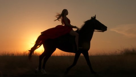 Young girl in red dress riding black horse against the sun. Rider with her stallion trotting across a field at sunset. Long gown blowing in the wind. Horseback riding in slow motion.