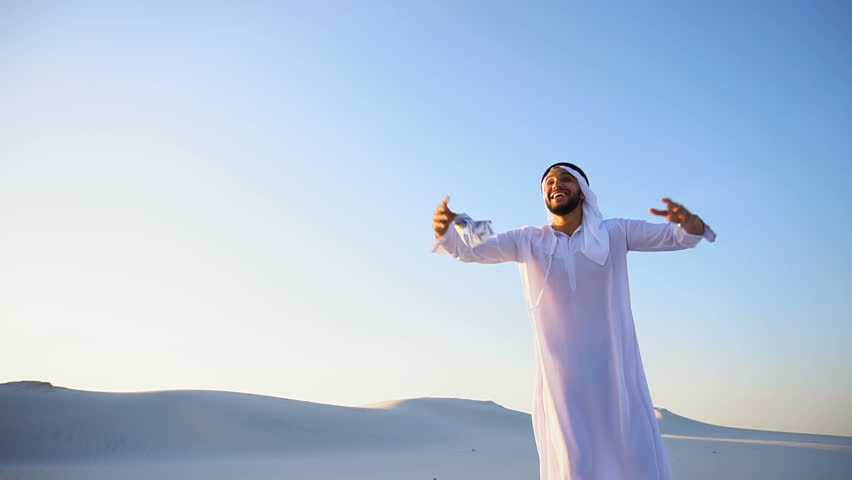Stately young male Arab man in good mood conducts financial training of money, smiles and laughs joyfully launches money to wind, standing in middle of bottomless desert with white sand on sunny