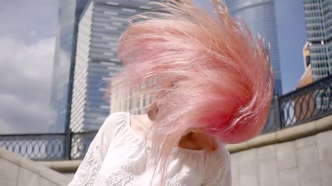 slow motion 500 frames a second. young cute girl with dyed pink color hair waving in the wind with his head. hair fade on the sides. on the background of the business center of the city