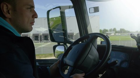 Inside of Cabin View of the Professional Truck Driver Driving His Big Vehicle on the Road. Industrial Warehouses are Seen out of the Window.