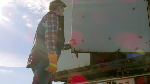 Truck Driver Closes Doors of His Truck Cargo Trailer. Professional Driver Wears Heavy Duty Gloves. Shot on RED EPIC-W 8K Helium Cinema Camera.