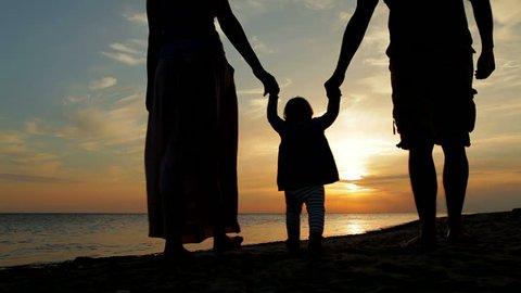 Happy family walking on sea coast. Silhouettes sunset.