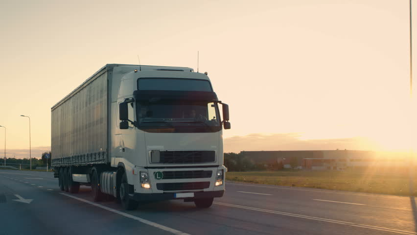 Follow-up Shot of a Semi-Truck with Cargo Trailer Moving on a Highway. White Truck Drives Through Industrial Warehouse Area in Early Hours of the Morning. Shot on RED EPIC-W 8K Helium Cinema Camera. #29801071