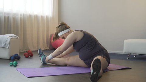 Overweight young woman warming up before doing set of exercises, losing weight