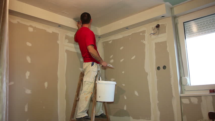 Painting Contractor At Work   Interior Decoration. Craftsman Arranging An  Apartment. Installing Dry Wall. Man Applying Plaster On A Dry Wall.