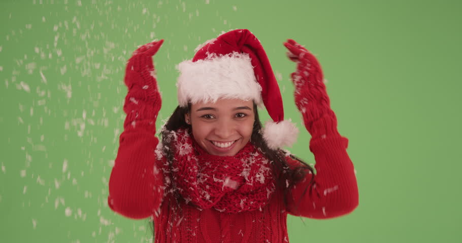 Millennial Latina throwing snow in the air on green screen. On green screen to be keyed or composited.