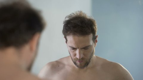 Man looking at his mirror reflection with hatred and shame, feeling guilty