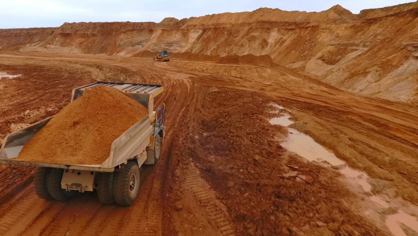 Mining truck transporting sand at sand quarry. Aerial view of mining machinery moving at sand mine. Sand work in mining industry  | Shutterstock HD Video #29822251