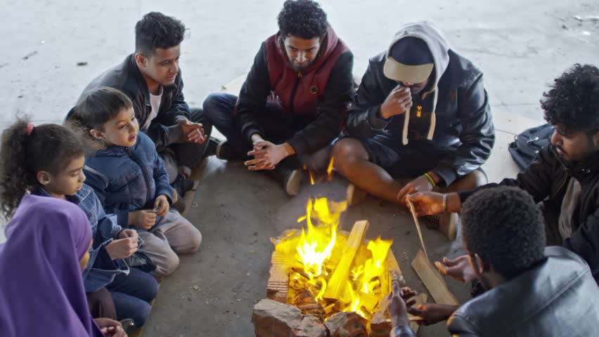 PAN with top view of Syrian men in jackets and little children with their Muslim mother in purple niqab sitting by fire in abandoned building