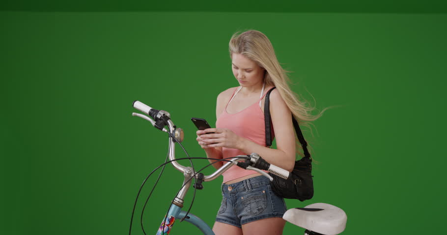 Lovely young California woman at beach texting bicycle owner to pick up his bike on green screen. On green screen to be keyed or composited.