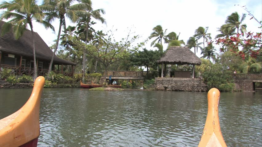 Polynesian canoes in a tropical pool in Oahu, Hawaii. Palm trees and tropical huts. Polynesian Cultural Center, Hawaii number one tourist attraction. Show the various islands of Polynesia.
