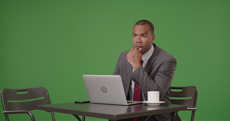 A black businessman works on his laptop while sipping coffee on green screen. On green screen to be keyed or composited. | Shutterstock HD Video #29851351
